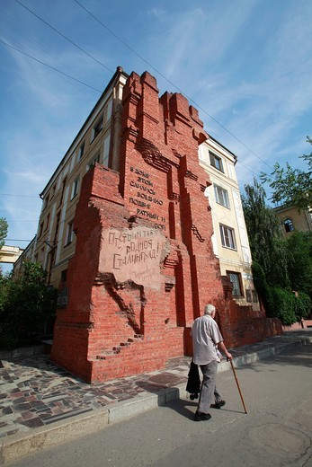 Stock Photo: 1566-966858 Man walking by brick wall with cryllic inscription, Volgograd, Russian Federation