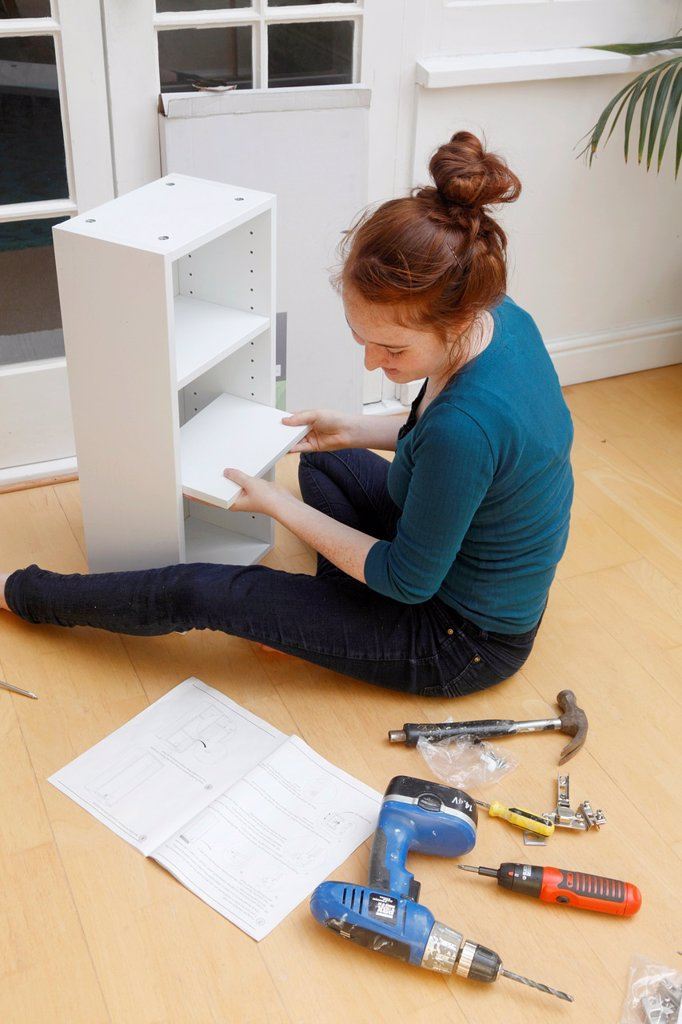 Young girl making a cabinet from a ´flat Pack´ DIY kit : Stock Photo
