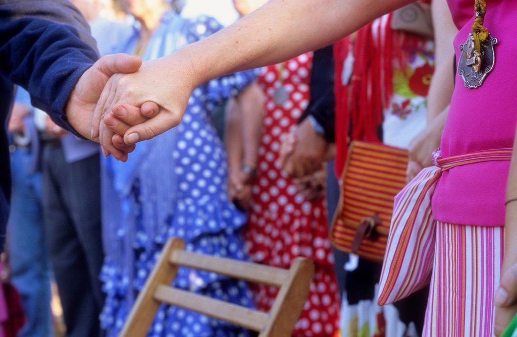 Detail of the hands of two pilgrims, morning Mass at the camp in Cerro del Trigo,Romeria del Rocio, pilgrims on their way through the Doñana National Park, pilgrimage of Sanlúcar de Barrameda brotherhood, to El Rocío, Almonte, Huelva province, Andalucia : Stock Photo