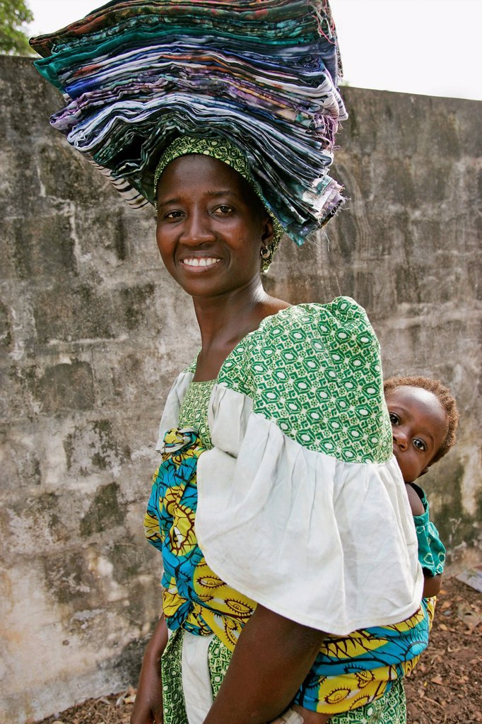 Fula woman in carries folded cloth on head and baby on back Bakau The Gambia : Stock Photo