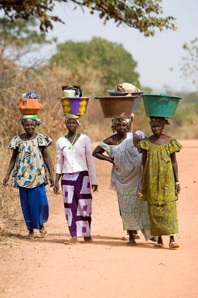 Women carry basins and goods on head bush road The Gambia : Stock Photo