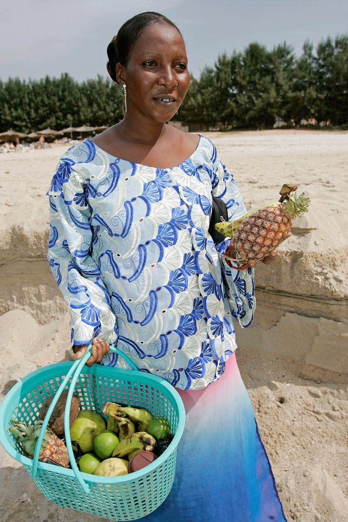 Woman fruit vendor in traditional dress peels pineapple The Cape beach Bakau The Gambia : Stock Photo