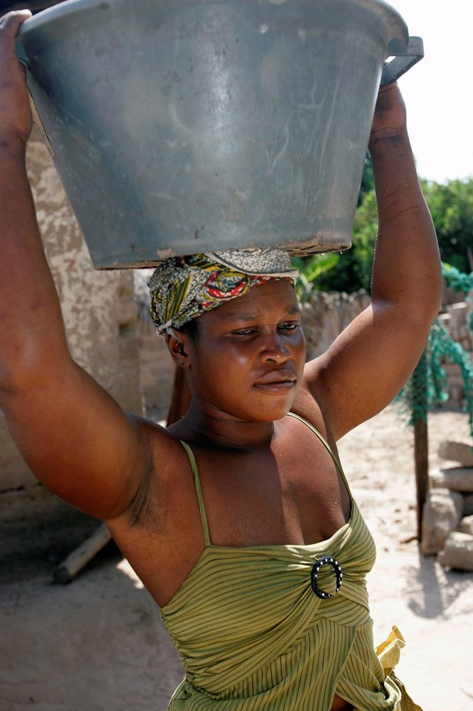 Woman carries large bowl on head Berending village south of The Gambia : Stock Photo