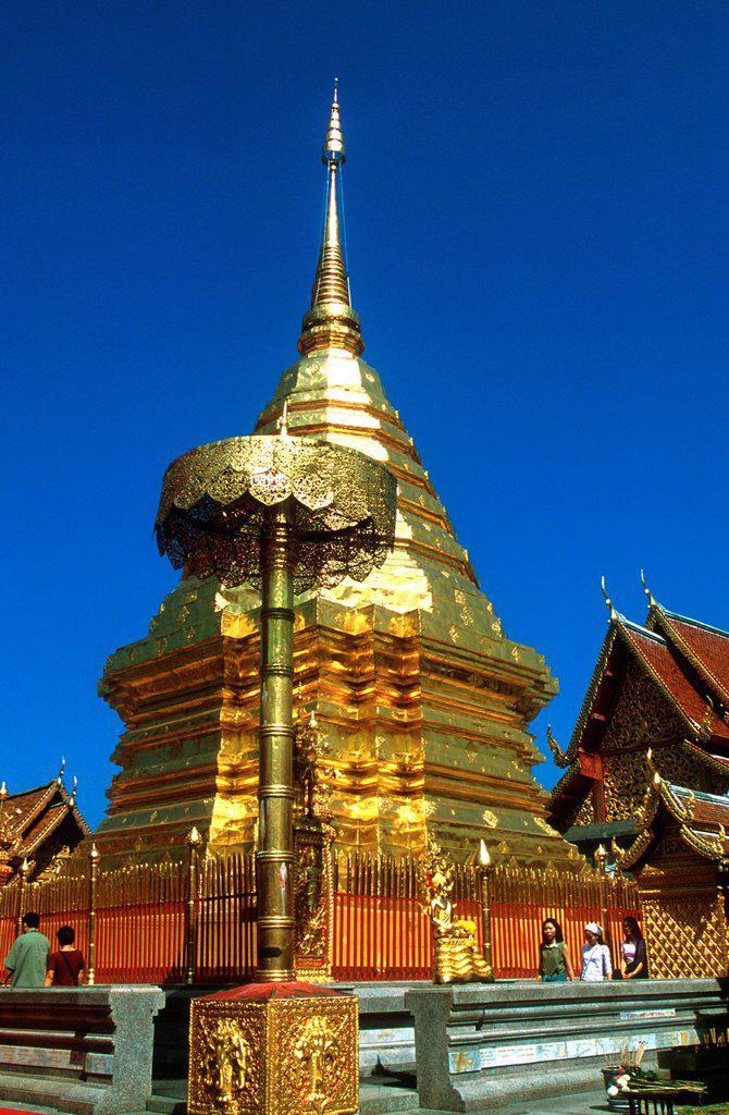 Stock Photo: 1566-970010 Devotees pray while walking round golden chedi Wat Phrathat Doi Suthep Chiang Mai Thailand
