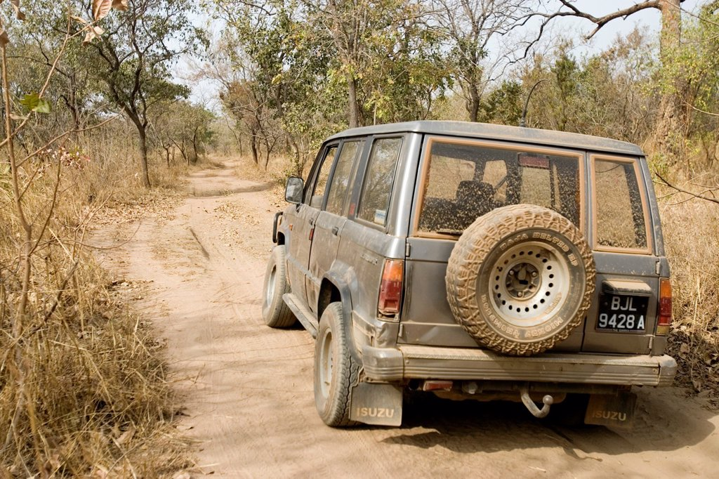 Dusty four wheel drive vehicle on bush track near Tendaba Camp Gambia River The Gambia : Stock Photo