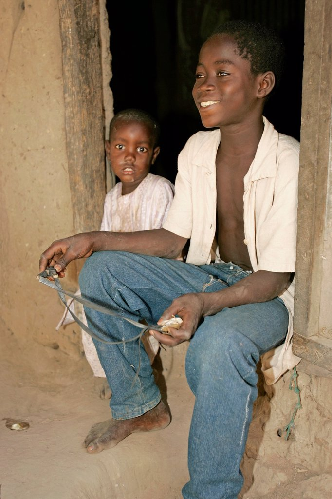 Boy in doorway with catapult Berending village south of The Gambia : Stock Photo