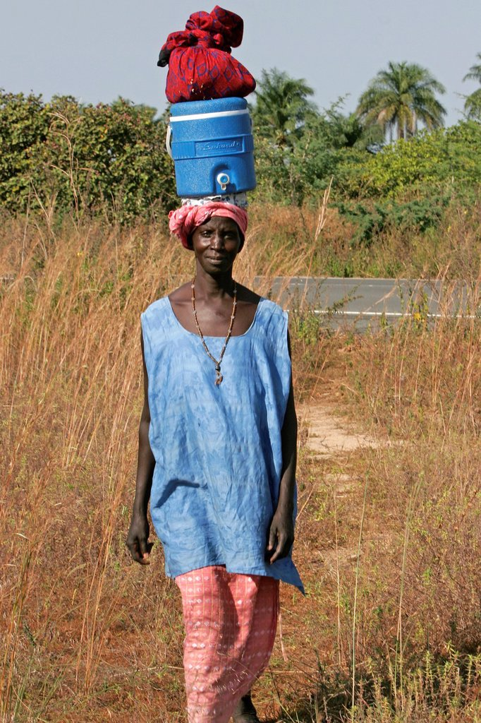 Stock Photo: 1566-971647 Woman carries belongings atop liquid dispenser on head near Kartong The Gambia