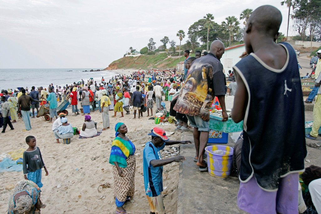 Crowds gather on beach for arrival of fishing boats Bakau The Gambia : Stock Photo