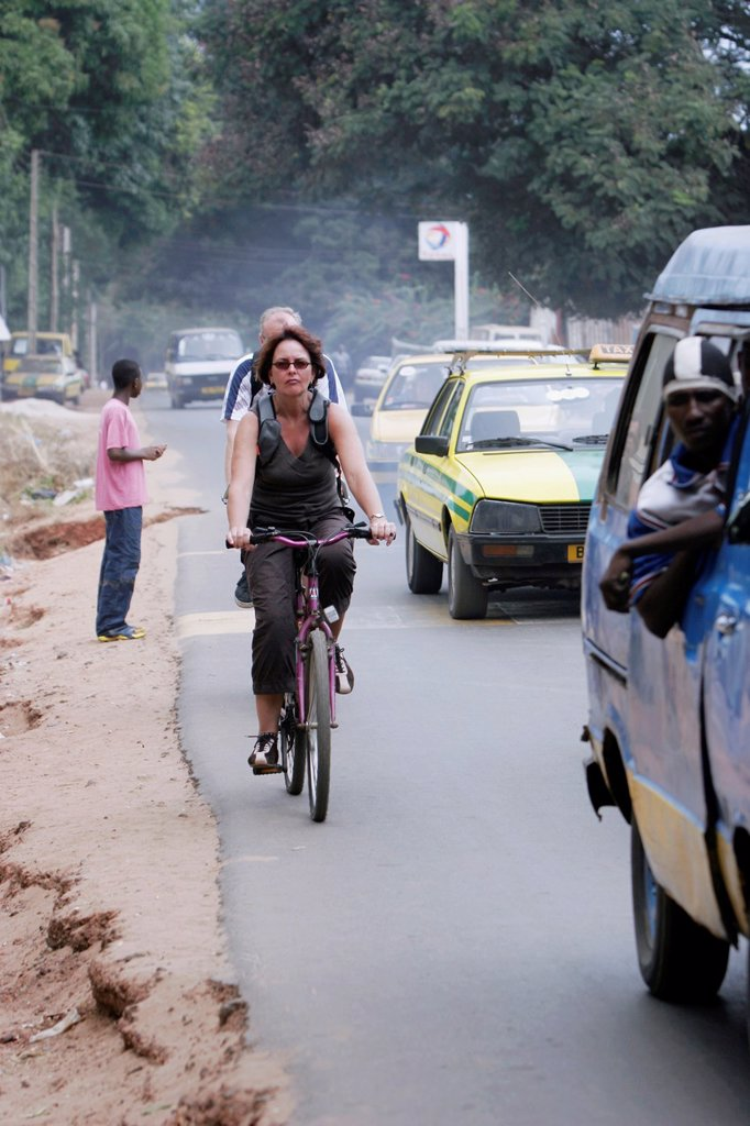Visitors ride in traffic fumes on busy street Bakau The Gambia : Stock Photo