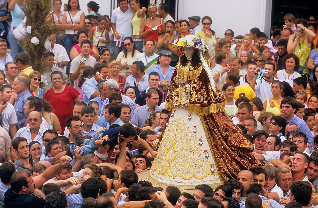 El Rocío Romería pilgrimage,Special procession,once every seven years the virgin of el Rocío travels from El Rocío to Almonte where he spends a few months, to finally go back to El Rocío,procession trip from el Rocío to Almonte,boy is carried over the cro. El Rocío Romería pilgrimage,Special procession,once every seven years the virgin of el Rocío travels from El Rocío to Almonte where he spends a few months, to finally go back to El Rocío,procession trip from el Rocío to Almonte,boy is carried  : Stock Photo