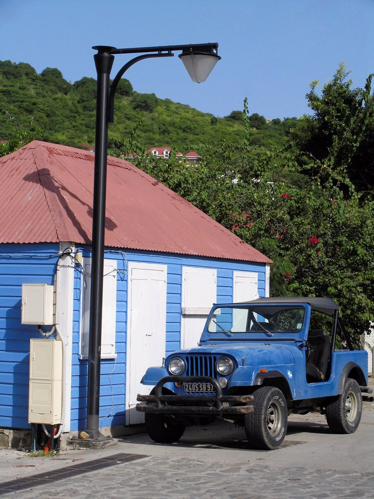 Stock Photo: 1566-973280 Blue wooden house with red tin roof white shutters and four wheel drive vehicle outisde Gustavia St Barts
