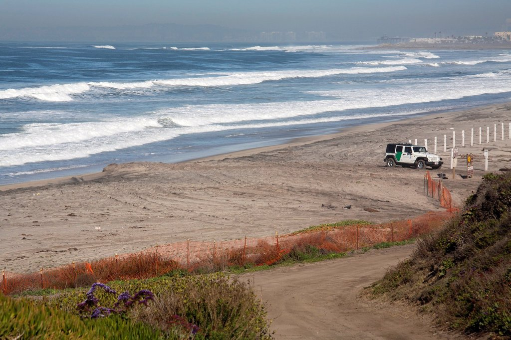San Ysidro, California - A U S  Border Patrol Jeep guards the beach at the Pacific Ocean, just north of the border fence  The hotels of San Diego can be seen faintly in the background : Stock Photo