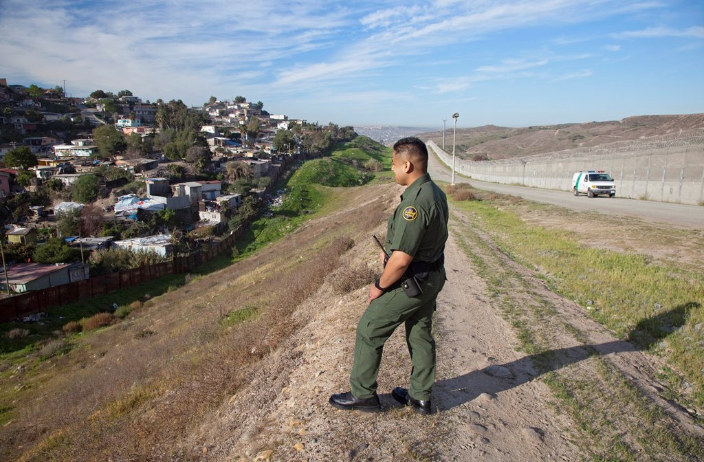 Stock Photo: 1566-973764 San Ysidro, California - U S  Border Patrol agent Joe Velasquez in the area between the old and new border fences between the United States and Mexico  A Tijuana neighborhood is across the old fence at left