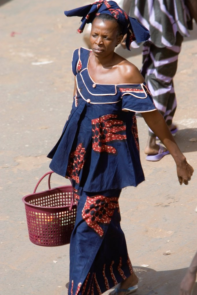 Stock Photo: 1566-974030 Woman in tradional off shoulder costume and head scarf walking with plastic shopping basket Serekunda Market The Gambia