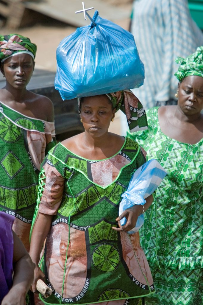 Stock Photo: 1566-974031 Woman in green traditional clothes carries plastic wrap bundle on head Serekunda Market The Gambia