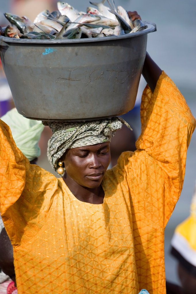 Stock Photo: 1566-974038 Young women carry basins of fresh fish on head up beach to market as open fishing boats arrive with catch Tanji The Gambia