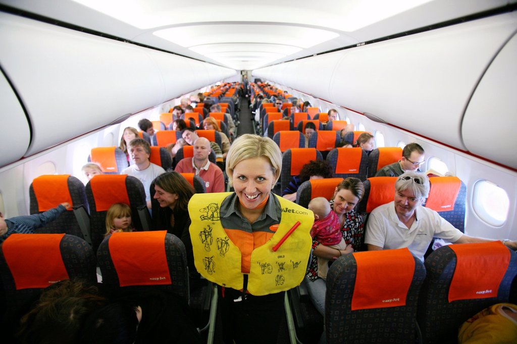 Stock Photo: 1566-975952 Stewardess presenting safety equipment on board editorial use only, no negative publicity