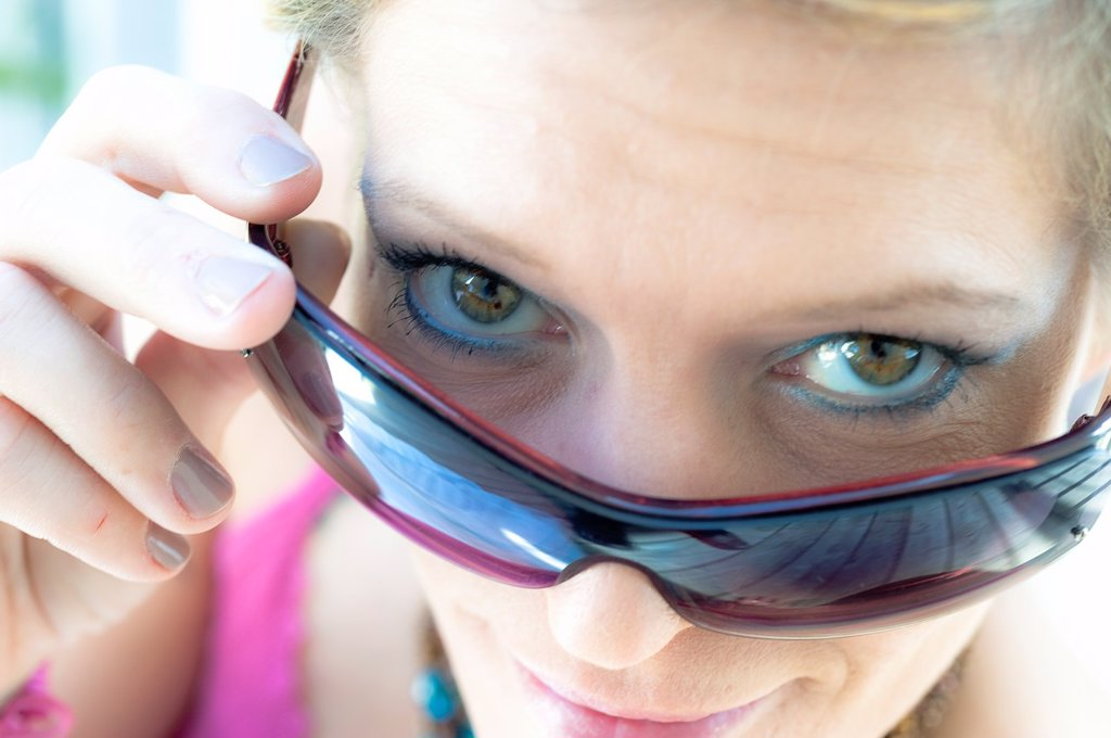 Stock Photo: 1566-976156 41 year old blond woman looking over her sun glasses