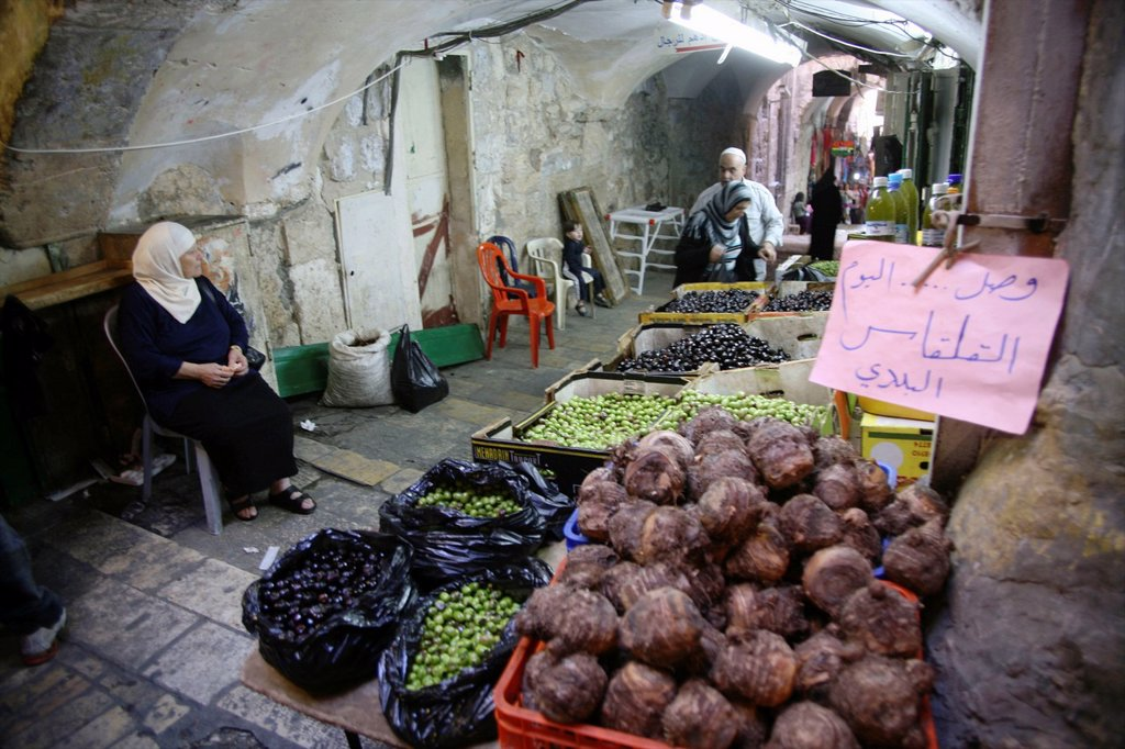 Stock Photo: 1566-976360 A woman selling olives and more at a market in the old city section of Jerusalem