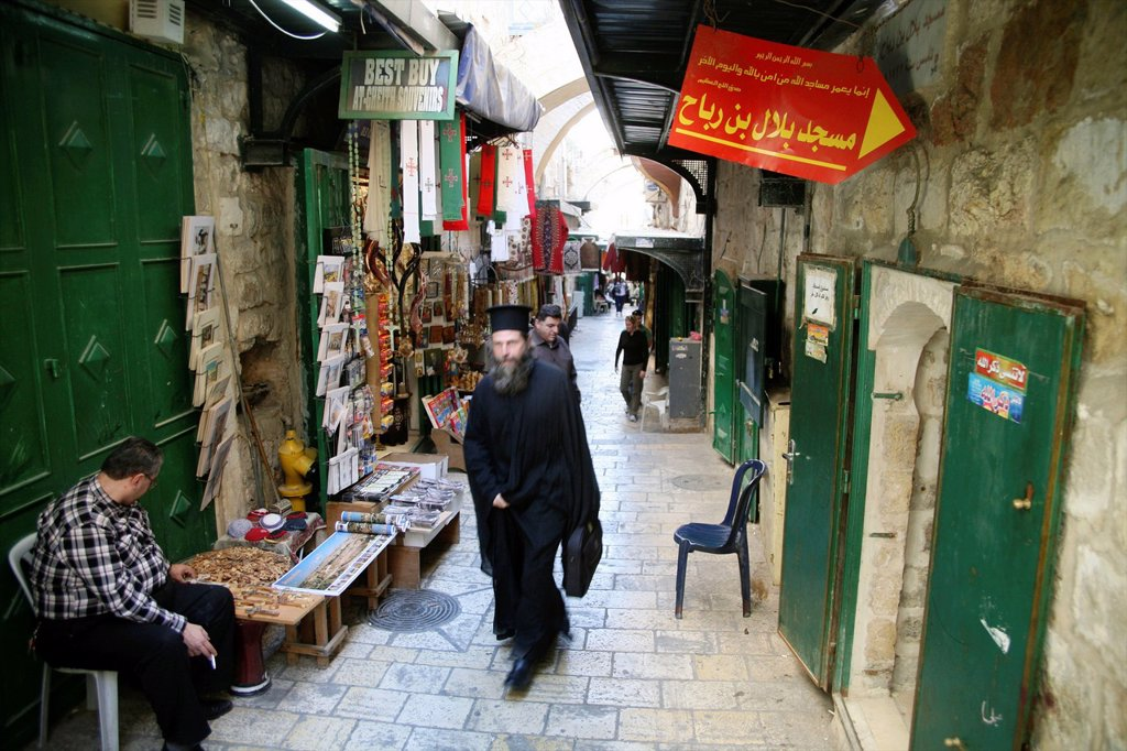 Stock Photo: 1566-976362 A man in traditional robes walks through a market in the old city section of Jerusalem