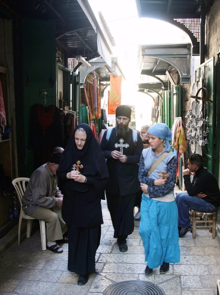 A group holding crosses walks through a market in the old city section of Jerusalem : Stock Photo