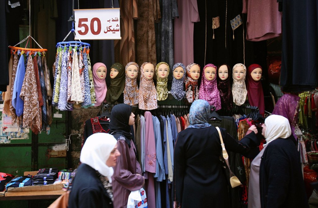 Stock Photo: 1566-976370 Women shop for clothes in front of a headscarf display at a market in the old city section of Jerusalem