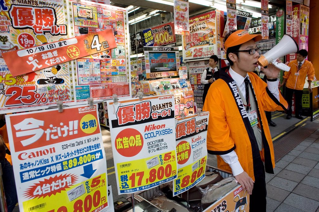 Stock Photo: 1566-977353 Japanese man announce sales at an electronic shopping mall in the heart of Tokyo, Japan