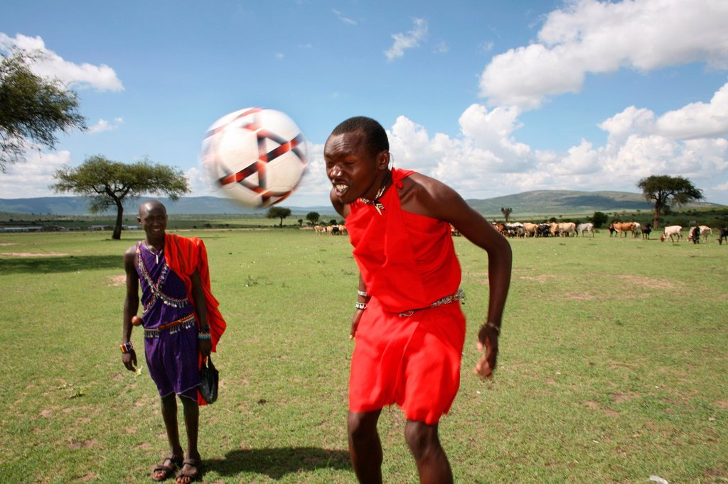 Stock Photo: 1566-977506 Football is opne of the most popular activities among the Massai tribe in south kenya Whenever their cows are brought in the village, the boys play football Also young Massai children from the nearby primary school play football every schoolbreak and afte