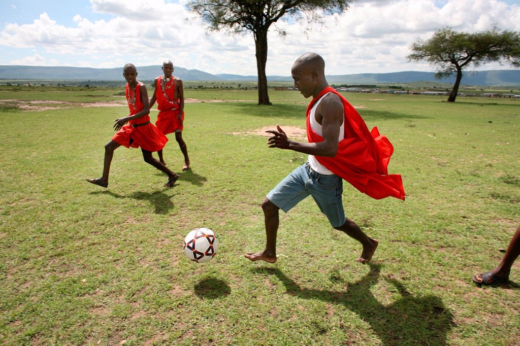 Stock Photo: 1566-977523 Football is opne of the most popular activities among the Massai tribe in south kenya Whenever their cows are brought in the village, the boys play football Also young Massai children from the nearby primary school play football every schoolbreak and afte