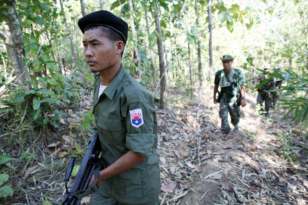 Stock Photo: 1566-977835 KNLA soldiers patrolling near the border with Thailand In Myanmar Burma, thousands of people have settled near the border as a result of oppression in their homeland Around 200 Burmese displaced people have settled in La Per Her, a village on the Burmese
