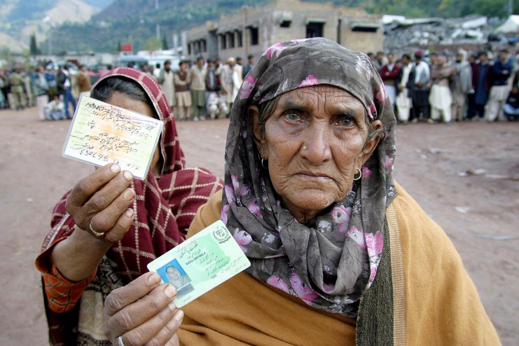 Stock Photo: 1566-977866 Women showing their ID cards, hoping to get also food during a distribution in Hatian, Kashmir, Pakistan On 8 october 2005, a severe earthquake hit Northern Pakistan Pakistan controlled Kashmir More than 70,000 people died and 3 million people where hom