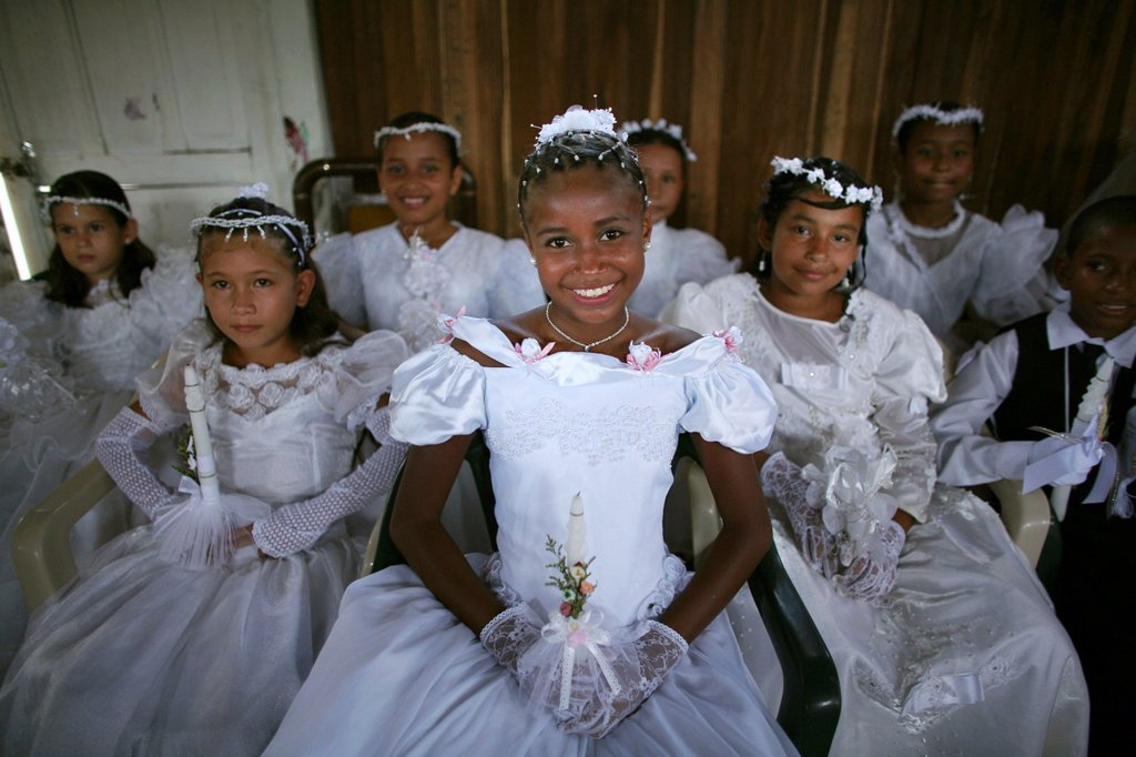 Children celebrate their first commune in the local slum church : Stock Photo