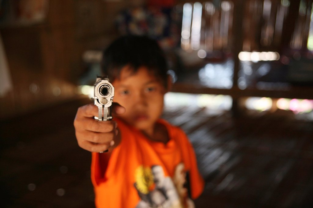 Stock Photo: 1566-978630 A young refugee aims a handgun at the camera Around 130,000 Burmese refugees have settled in Thailand due to opression in their homeland of Myanmar Burma Approximately 30,000 refugees now live in Mae Sot western Thailand and receive humanitarian aid Anoth