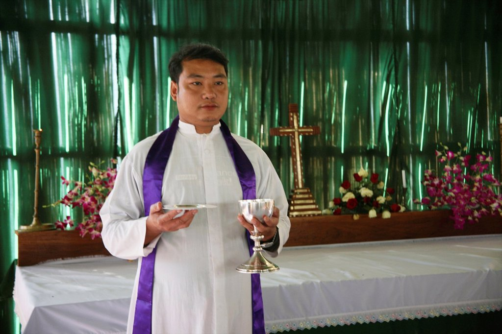Stock Photo: 1566-978631 A priest celebrates mass at the refugee camp Anglican church in Mae Sot Around 130,000 Burmese refugees have settled in Thailand due to opression in their homeland of Myanmar Burma Approximately 30,000 refugees now live in Mae Sot western Thailand and rec