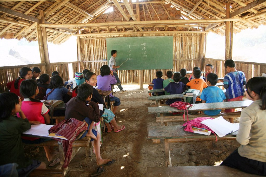 Stock Photo: 1566-978829 A teacher instructs pupils at a primary school in Mae Sot refugee camp Around 130,000 Burmese refugees have settled in Thailand due to opression in their homeland of Myanmar Burma Approximately 30,000 refugees now live in Mae Sot western Thailand and rece