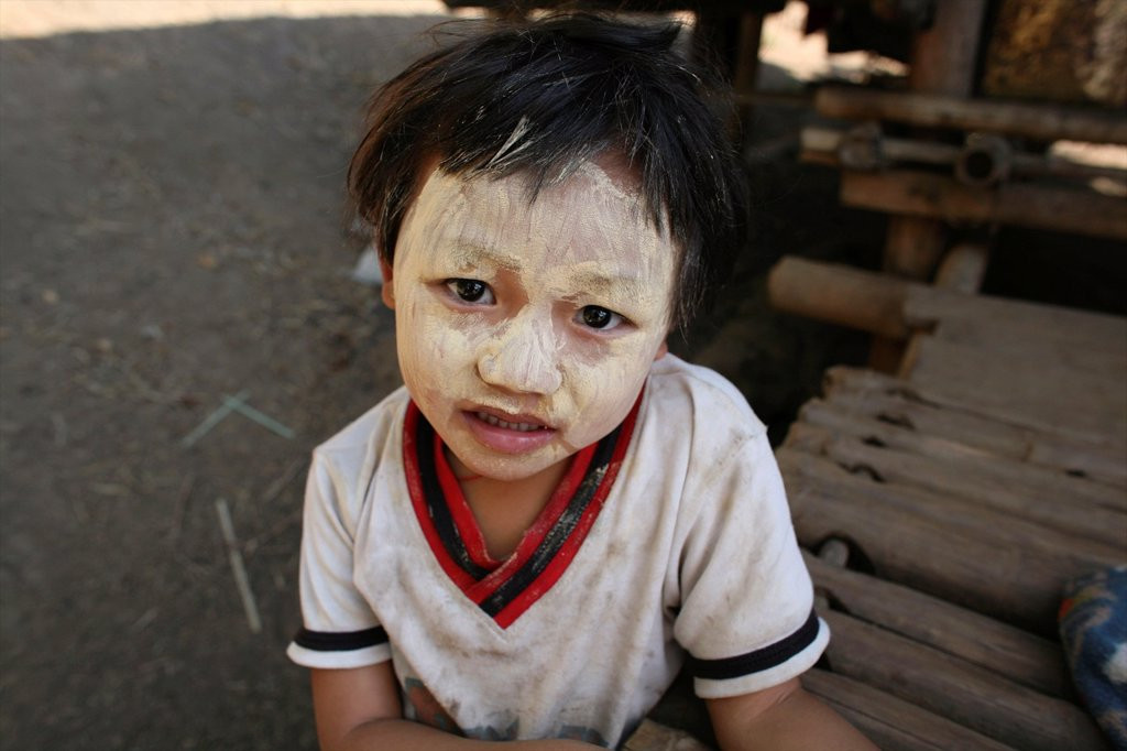Stock Photo: 1566-978986 A Burmese child with decorative face painting in the camp on the border with Thailand In Myanmar Burma, thousands of people have settled near the border as a result of oppression in their homeland Around 200 Burmese displaced people have settled in La Per