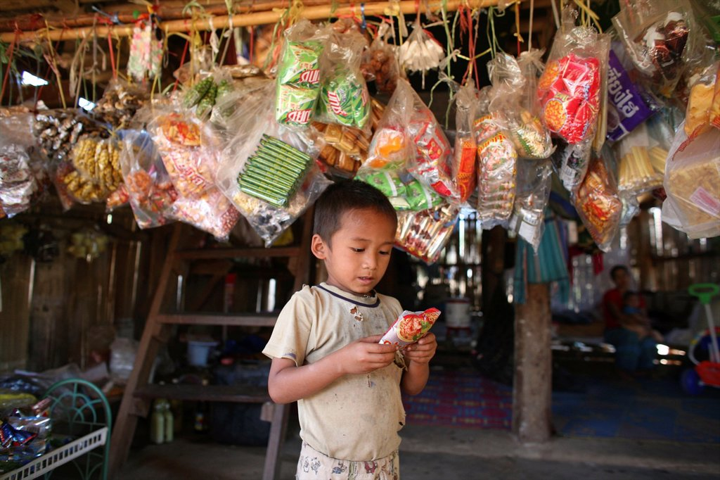 Stock Photo: 1566-978987 A child outside a shop in the displaced persons camp near the border with Thailand In Myanmar Burma, thousands of people have settled near the border as a result of oppression in their homeland Around 200 Burmese displaced people have settled in La Per He