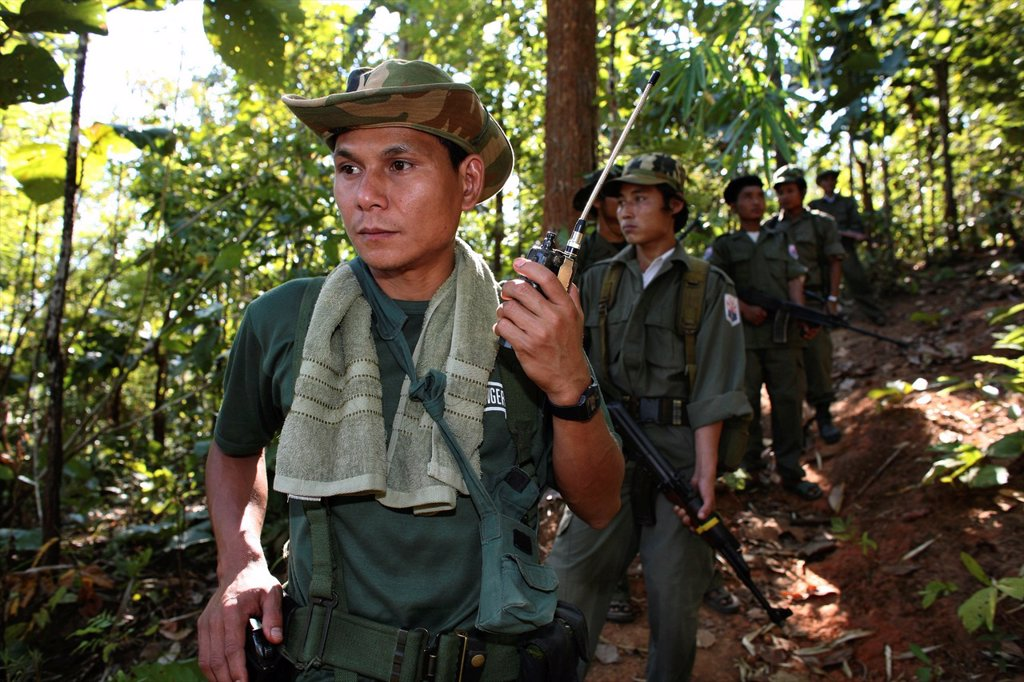 Stock Photo: 1566-978990 A KNLA soldier listening to a radio device near the border with Thailand In Myanmar Burma, thousands of people have settled near the border as a result of oppression in their homeland Around 200 Burmese displaced people have settled in La Per Her, a villa