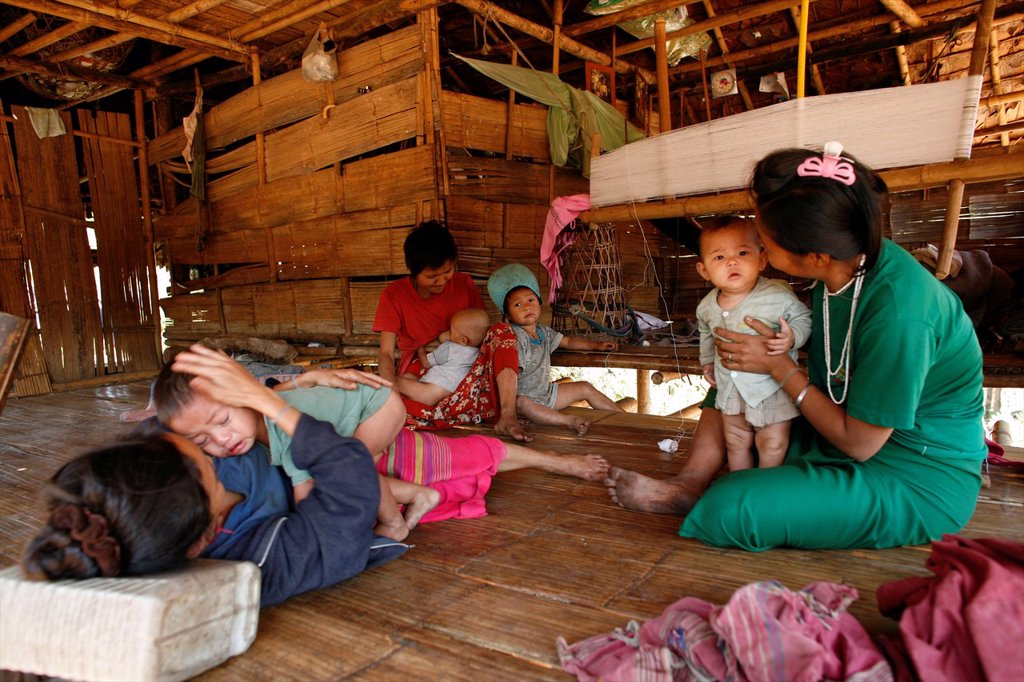 An extended Burmese family in their home near the border with Thailand In Myanmar Burma, thousands of people have settled near the border as a result of oppression in their homeland Around 200 Burmese displaced people have settled in La Per Her, a village : Stock Photo