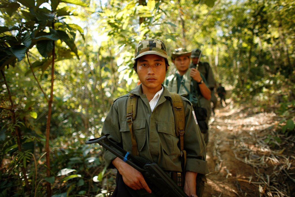 Stock Photo: 1566-979003 KNLA soldiers walk through the jungle In Myanmar Burma, thousands of people have settled near the border as a result of oppression in their homeland Around 200 Burmese displaced people have settled in La Per Her, a village on the Burmese side of the borde