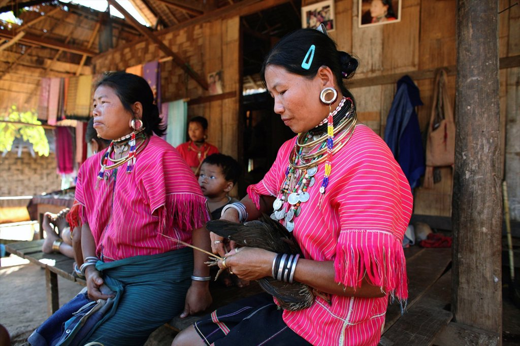 Burmese women gathered outside a house in the camp Approximately 300 Burmese refugees in Thailand are members of the indigenous group known as the Longnecks The largest of the three villages where the Longnecks live is called Nai Soi, located near Mae Hon : Stock Photo