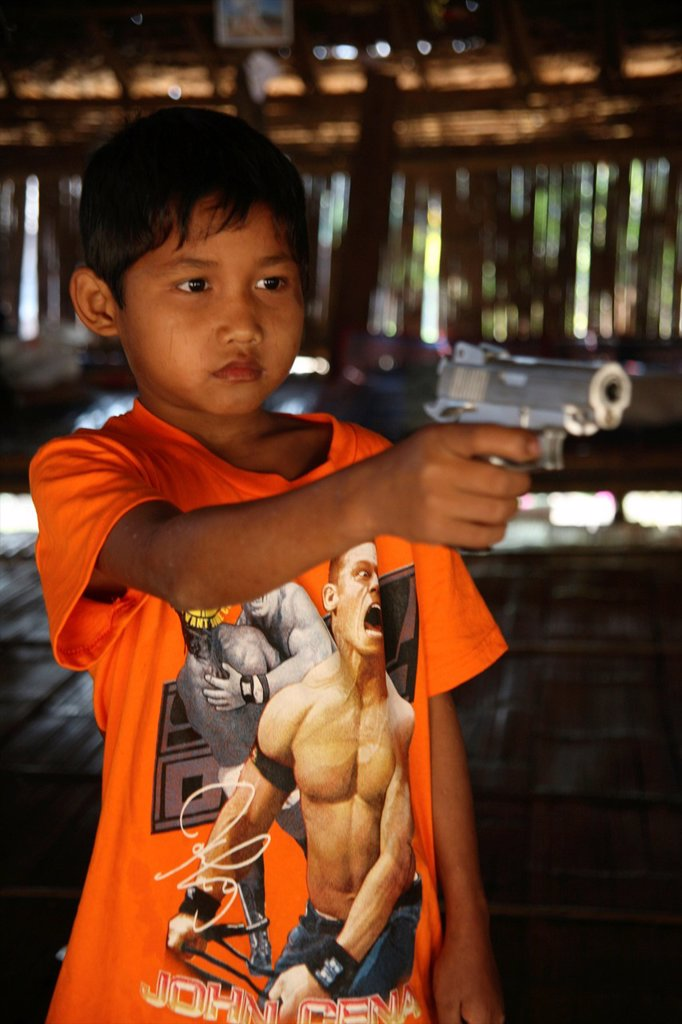 Stock Photo: 1566-979090 Refugee boy aims a gun in Mae Sot Around 130,000 Burmese refugees have settled in Thailand due to opression in their homeland of Myanmar Burma Approximately 30,000 refugees now live in Mae Sot western Thailand and receive humanitarian aid Another 200 Burm
