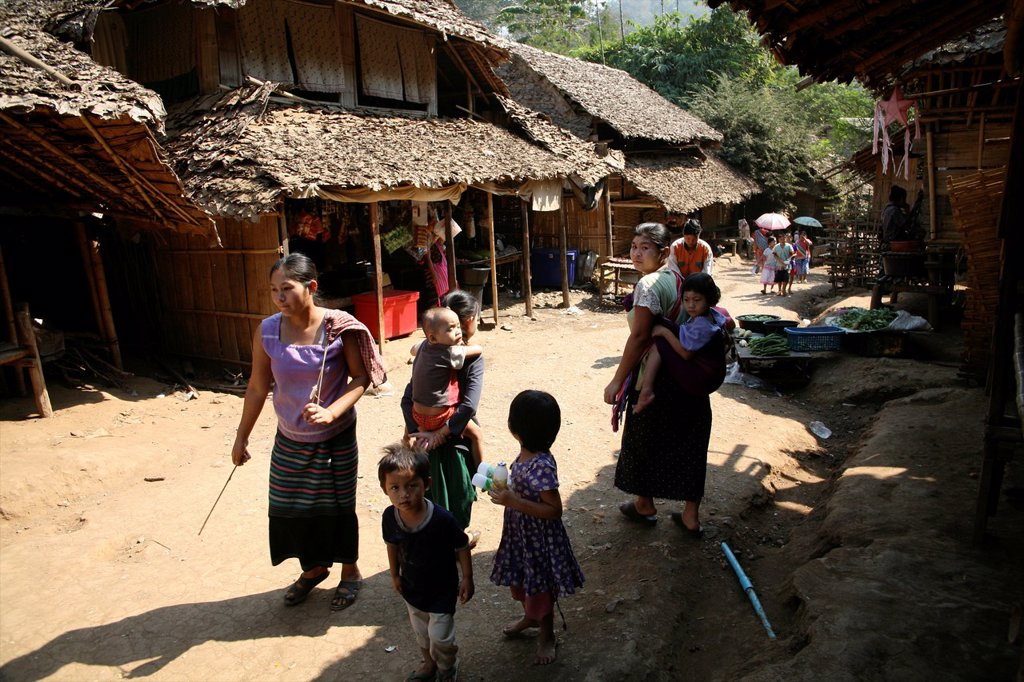 Stock Photo: 1566-979091 Refugees walk in Mae Sot Around 130,000 Burmese refugees have settled in Thailand due to opression in their homeland of Myanmar Burma Approximately 30,000 refugees now live in Mae Sot western Thailand and receive humanitarian aid Another 200 Burmese refug