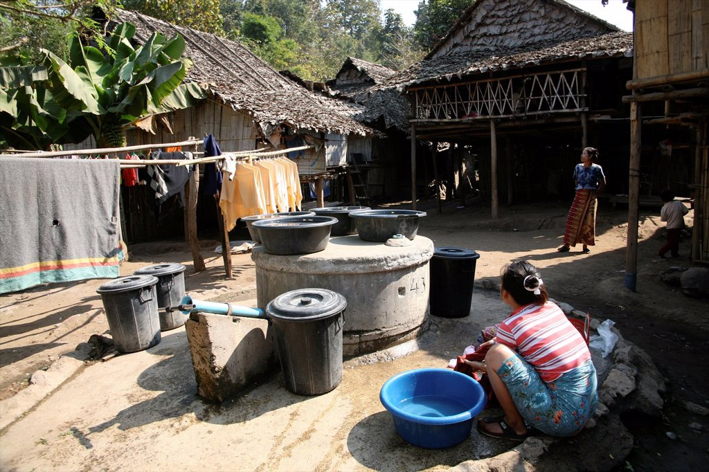 Stock Photo: 1566-979092 A refugee woman washes clothes in the camp Around 130,000 Burmese refugees have settled in Thailand due to opression in their homeland of Myanmar Burma Approximately 30,000 refugees now live in Mae Sot western Thailand and receive humanitarian aid Another