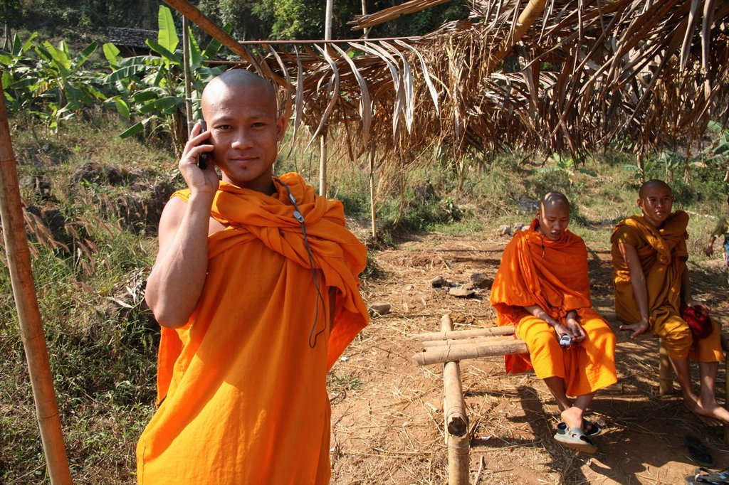 Stock Photo: 1566-979095 Buddhist monk on the phone with other monks in the background at Mae Sot refugee camp Around 130,000 Burmese refugees have settled in Thailand due to opression in their homeland of Myanmar Burma Approximately 30,000 refugees now live in Mae Sot western Th