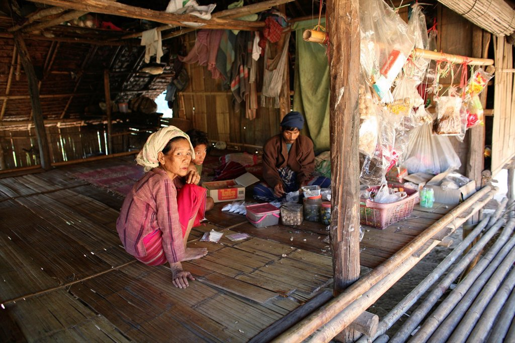 Stock Photo: 1566-979968 Burmese family in a hut in the displaced village near the Thai border In Myanmar Burma, thousands of people have settled near the border as a result of oppression in their homeland Around 200 Burmese displaced people have settled in La Per Her, a village