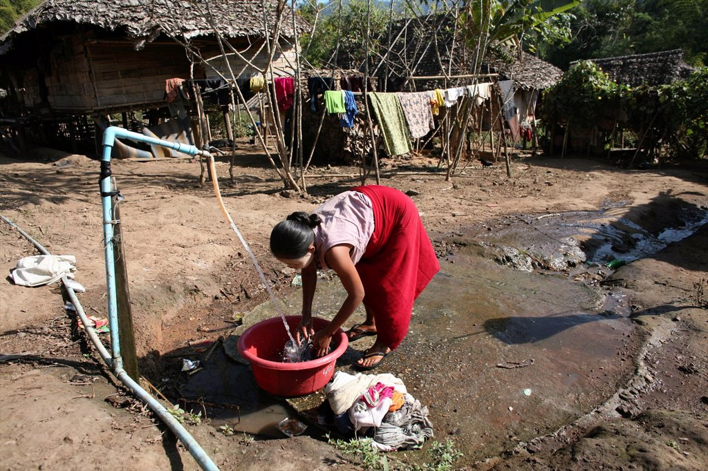Stock Photo: 1566-979970 A Burmese woman washes clothes in the displaced person camp near the border with Thailand In Myanmar Burma, thousands of people have settled near the border as a result of oppression in their homeland Around 200 Burmese displaced people have settled in La