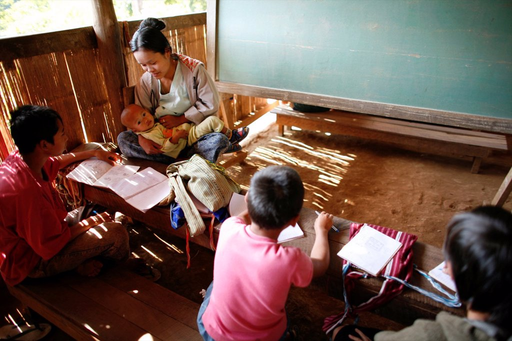 Stock Photo: 1566-979978 A teacher with her baby at the La Per Her village school in Myanmar In Myanmar Burma, thousands of people have settled near the border as a result of oppression in their homeland Around 200 Burmese displaced people have settled in La Per Her, a village on
