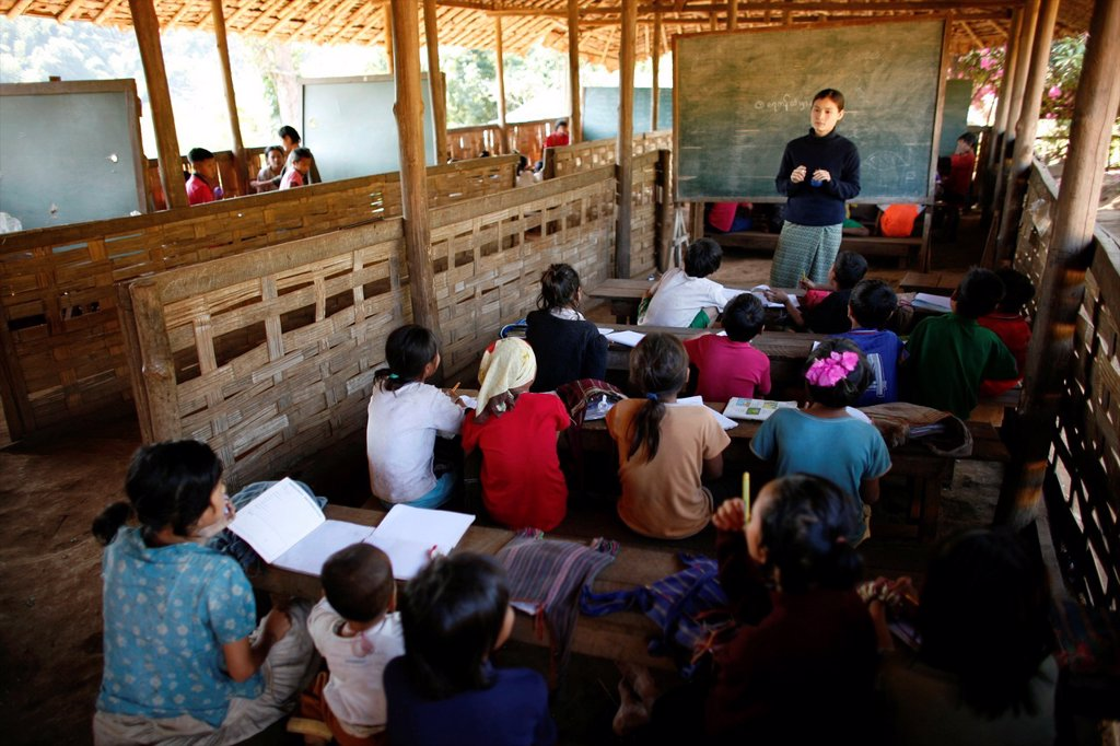 Stock Photo: 1566-979980 A teacher addresses her class in the village school in La Per Her In Myanmar Burma, thousands of people have settled near the border as a result of oppression in their homeland Around 200 Burmese displaced people have settled in La Per Her, a village on t