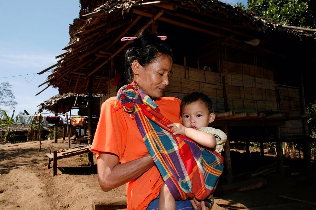 Stock Photo: 1566-979981 A Burmese woman carrying her baby in La Per Her In Myanmar Burma, thousands of people have settled near the border as a result of oppression in their homeland Around 200 Burmese displaced people have settled in La Per Her, a village on the Burmese side of